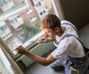 Remontoija ikkunoiden ja seinien kimpussa.