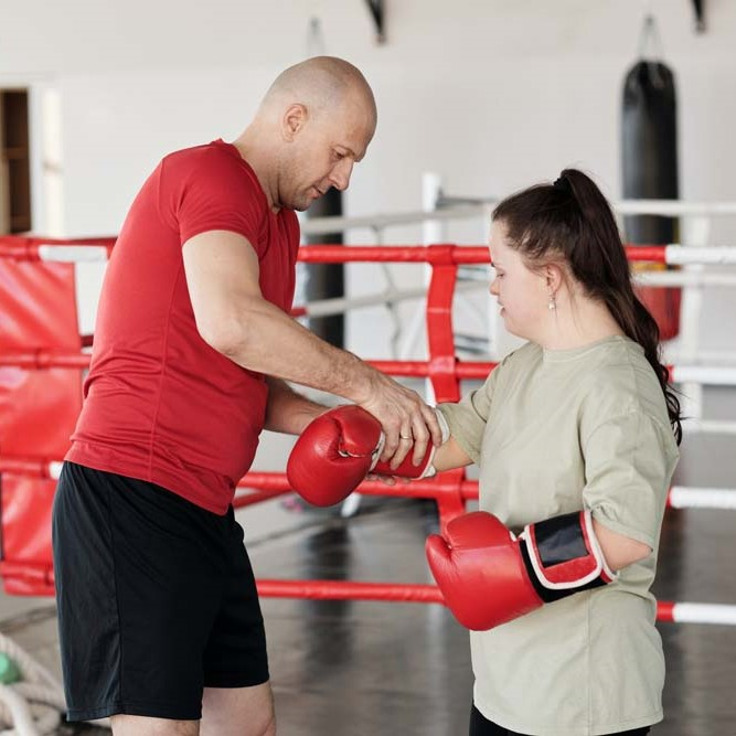 man helping girl with boxing gloves