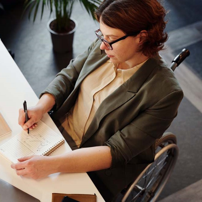 woman in wheelchair works at desk