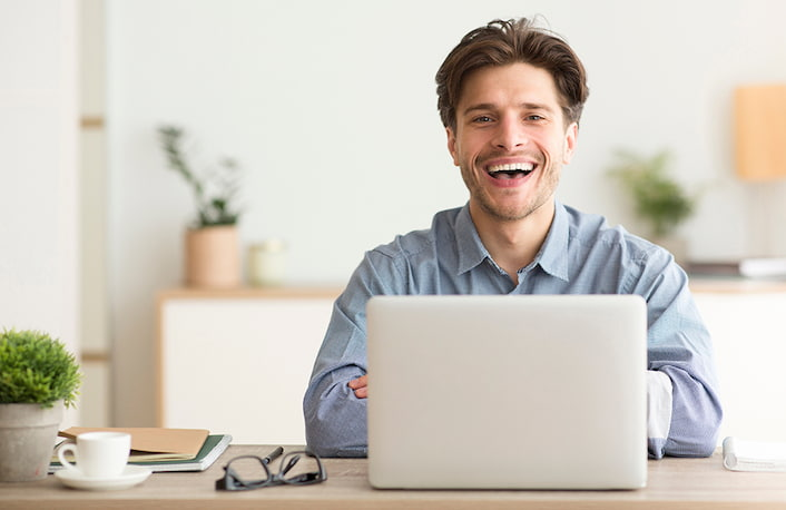 Man smiling with a laptop
