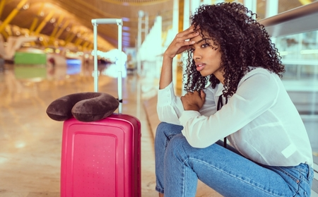 Young woman sitting with suitcase in airport looking unimpressed