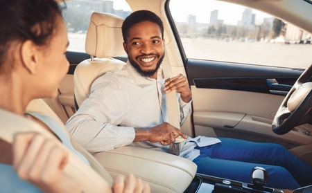 Male driver smiling at female passenger as they put on their seatbelts