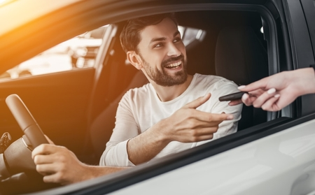 Man getting handed keys while in drivers seat
