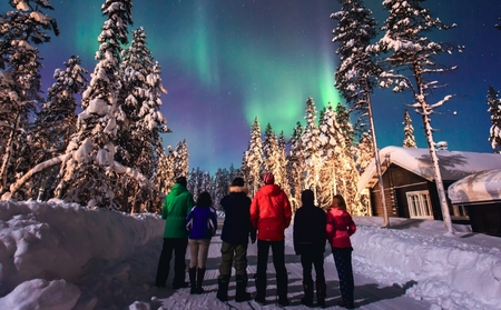 A group of people standing outside a cabin in the woods looking at the northern lights