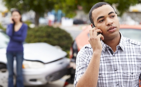 Young man calling insurance at the scene of an accident
