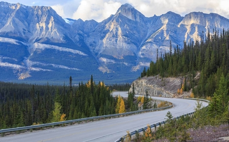 Scenic road in Canada with Rocky Mountains in background.