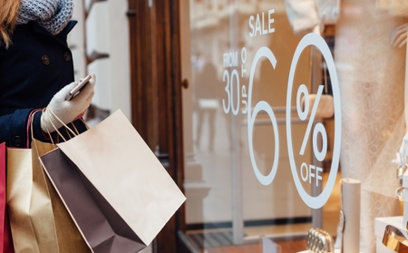 Person holding lots of shopping bags in winter outerwear in front of window with sale signs