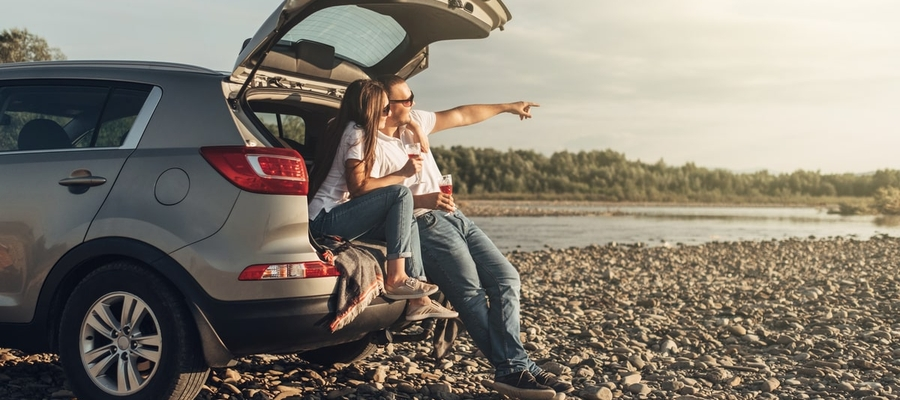 Couple sitting in the back of suv on the beach