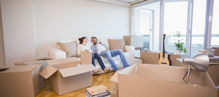 Young couple relax while unpacking in new home.