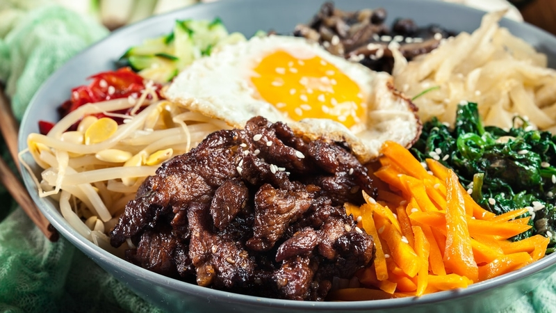 A bowl of bibimbap that includes eggs, meats and vegetables.