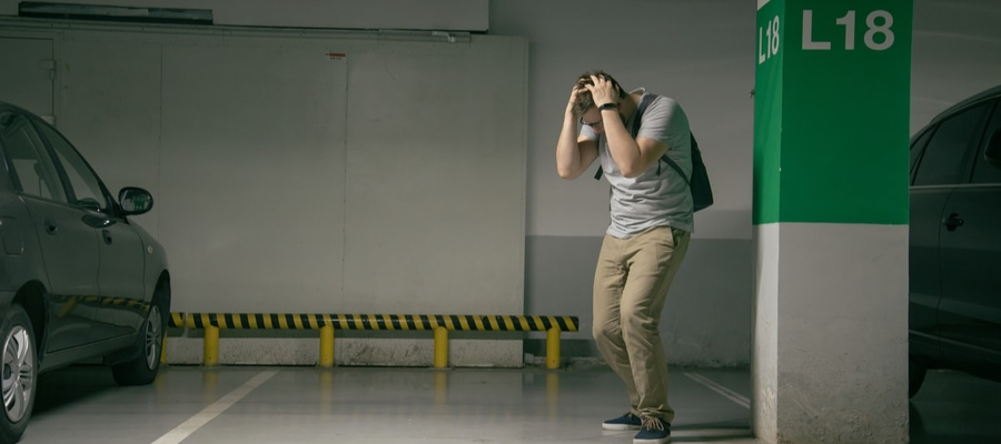 A young man at the parking spot in the underground parking garage where his car was parked but has since been stolen.