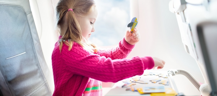 A young child playing with a puzzle while on an airplane.
