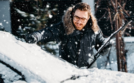 A man clearing snow off his car as it continues to snow.
