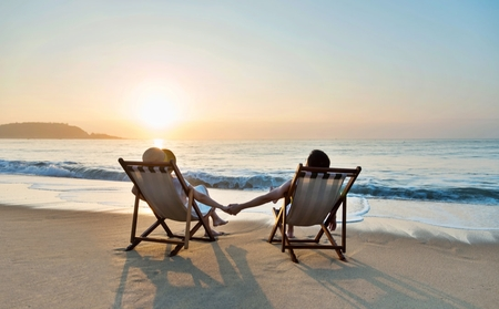 A couple holding hands while sitting in beach chairs looking out towards the ocean.