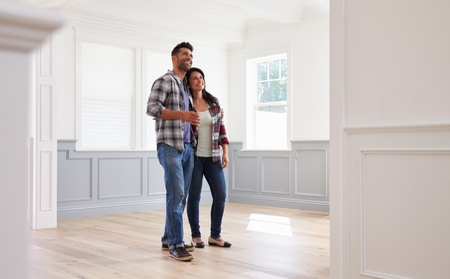 A couple looking at an empty home while the real estate is out of sight giving the proper social distance needed.