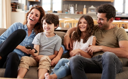 A family of four sitting on the couch getting ready to watch television.