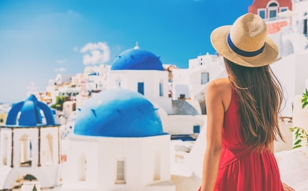 The view from behind a woman looking out towards a brightly coloured village in Greece.