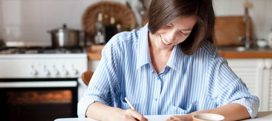 A woman sitting at her kitchen table writing out a list.