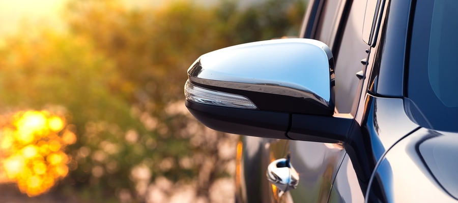 The sideview mirror of a new black pickup truck.