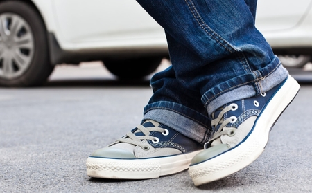 A close-up of a person's sneakers with a parked white car in the background.