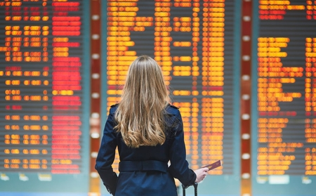 Woman looks at board of flight statuses at airport terminal