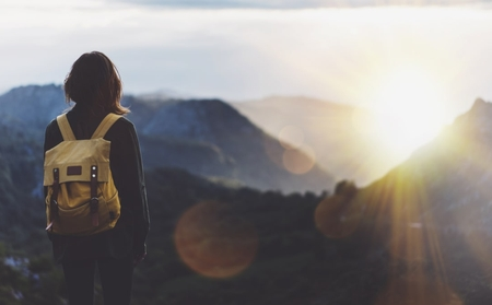 Woman with yellow backpack looking out on scenic mountains at sunset
