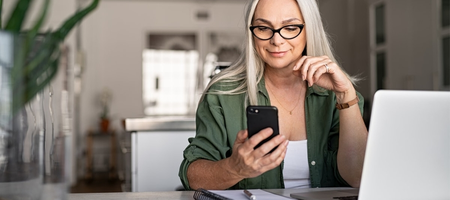 An older stylish woman sitting at her home office desk looking at her smartphone with her laptop in front of her.