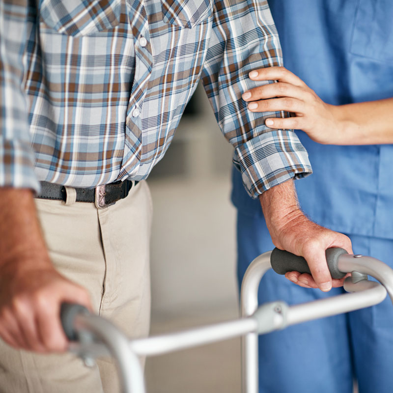 Senior man is assisted by nurse under skilled nursing care