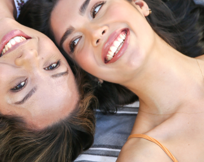 Two women laying down smiling