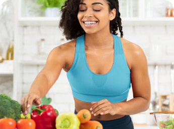 Woman in workout gear selecting fruit
