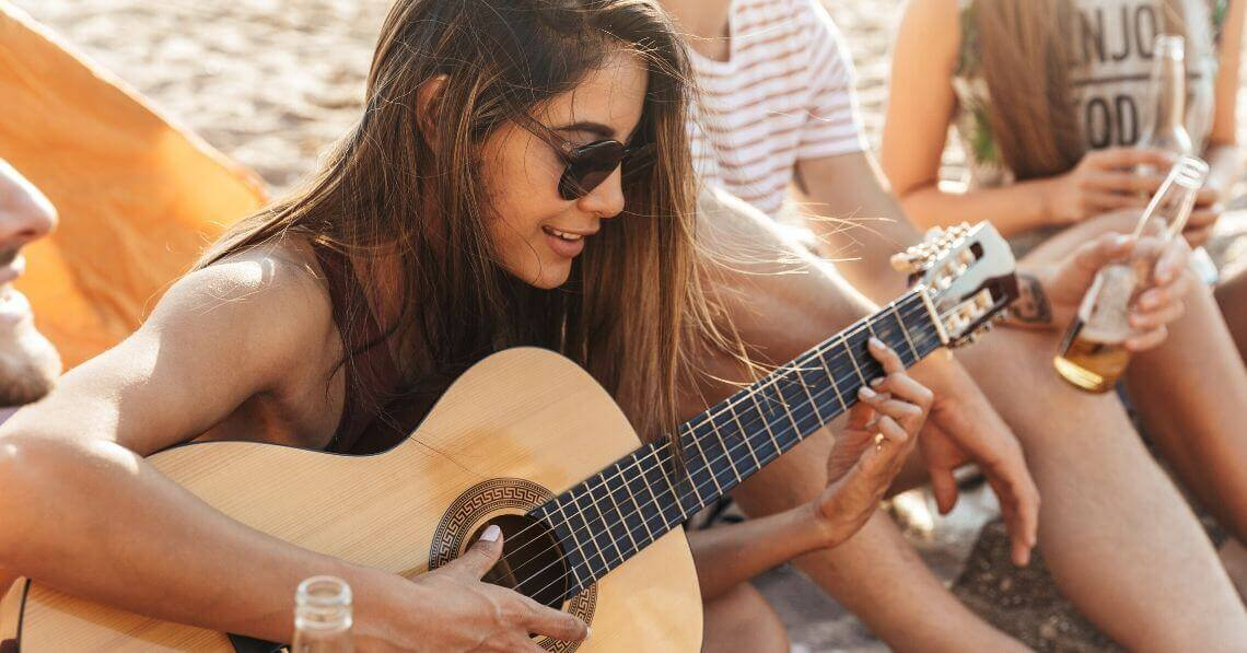 Young woman playing guitar at the beach party