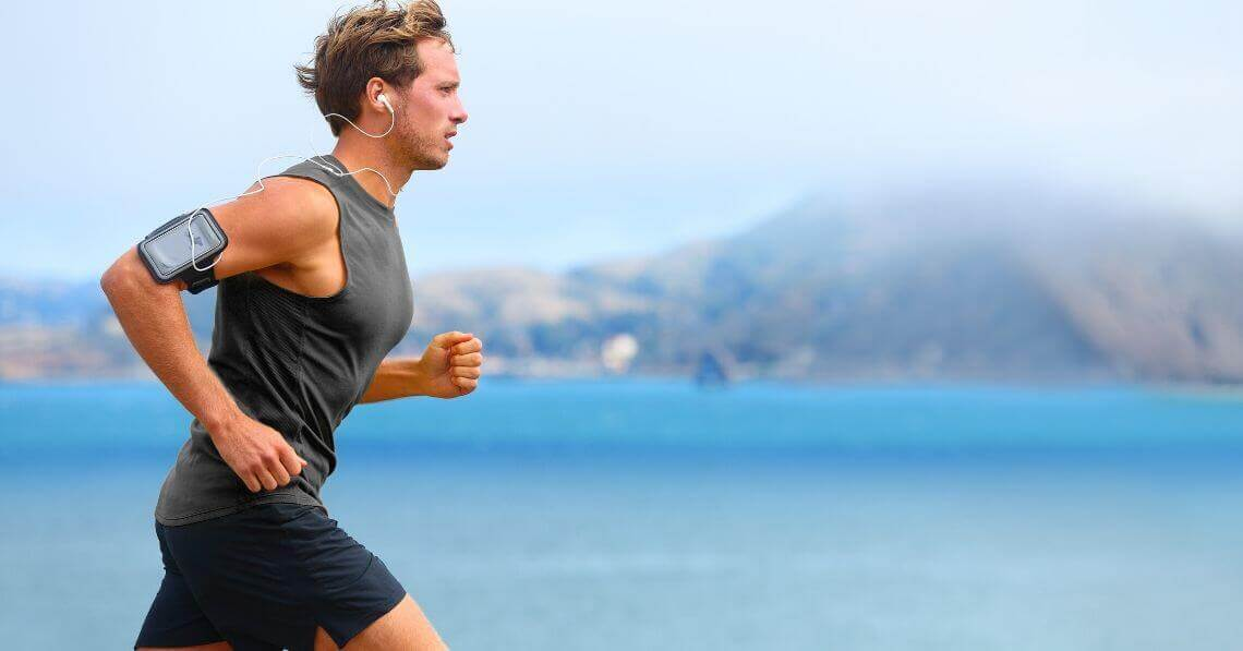 Young man running while listening to music