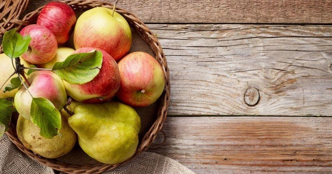 Apples and pears in a basket on a wooden table