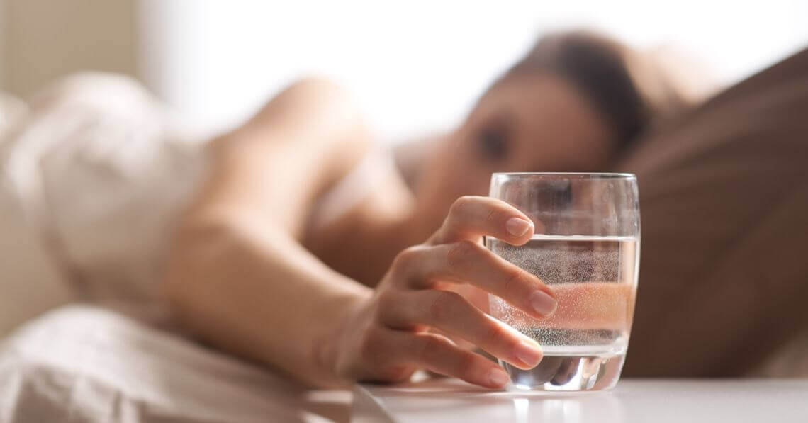 Young woman reaching for a glass of water in bed
