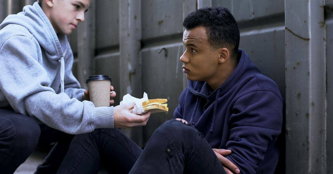 A young man giving a sandwich and a cup of coffee to a homeless man