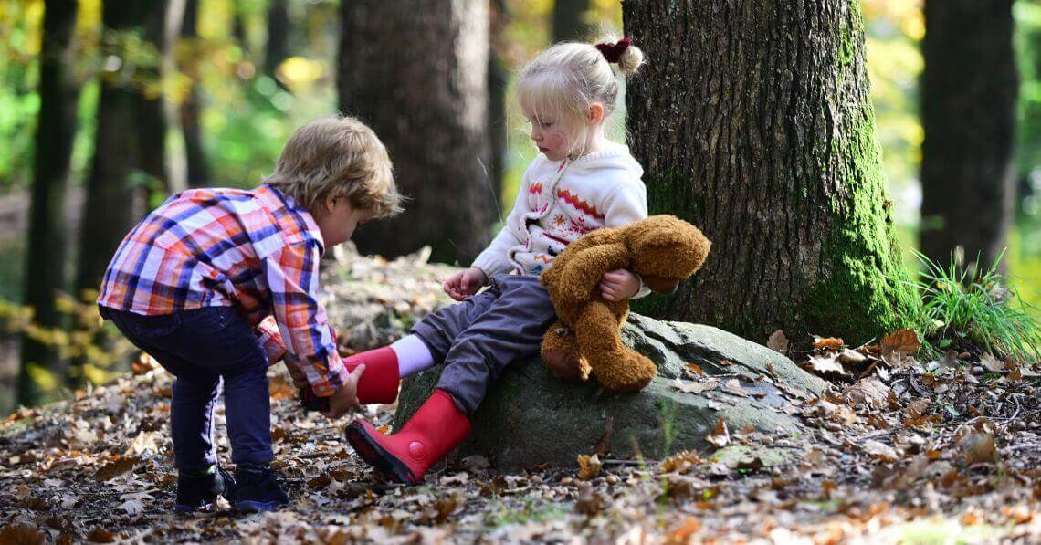 A toddler boy helping a toddler girl with her boots