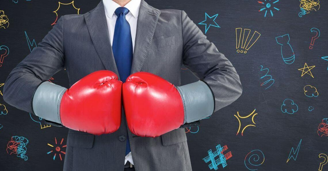 Man with boxing gloves in a suit is ready to fight