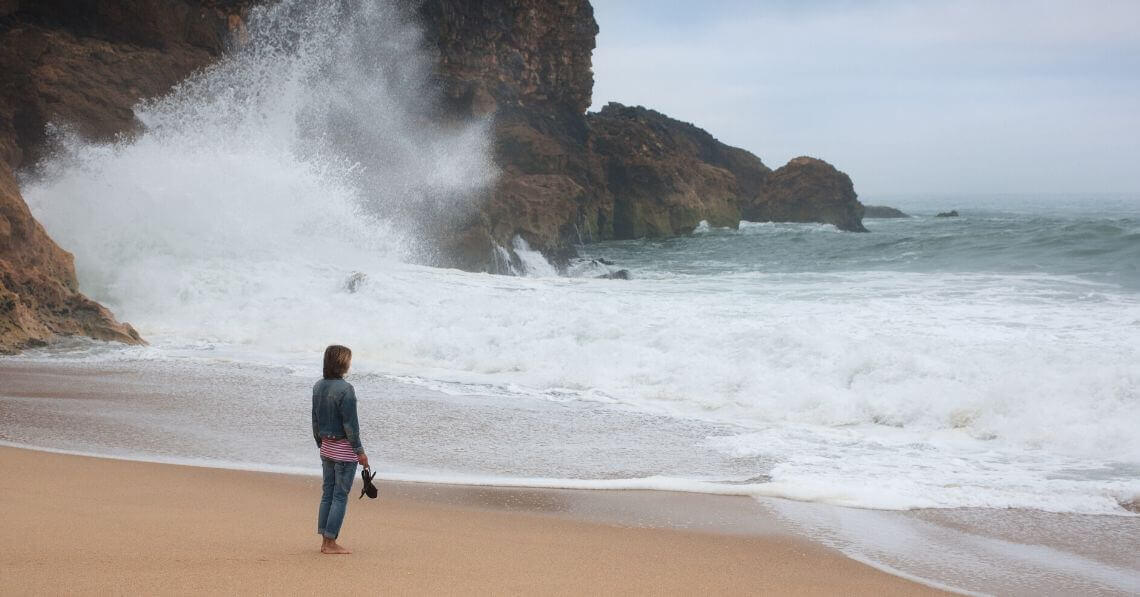 A woman standing by the ocean