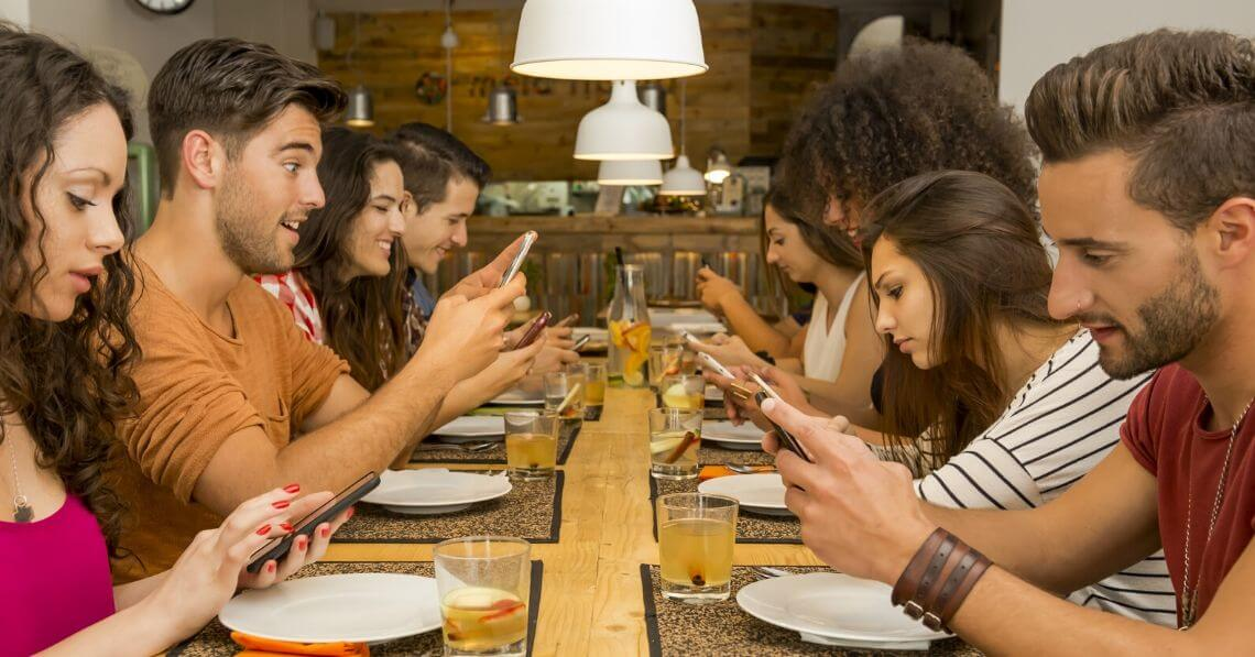 Young people at dinner table looking at their phones