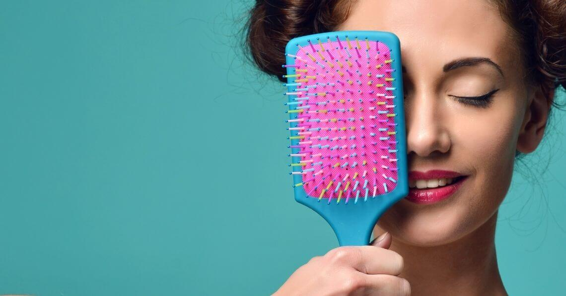 Playful young woman with a colorful hair brush