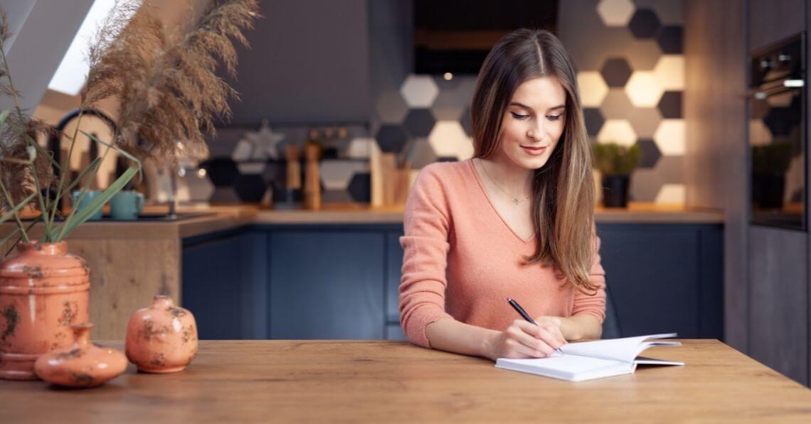 Woman writing on a gratitude journal