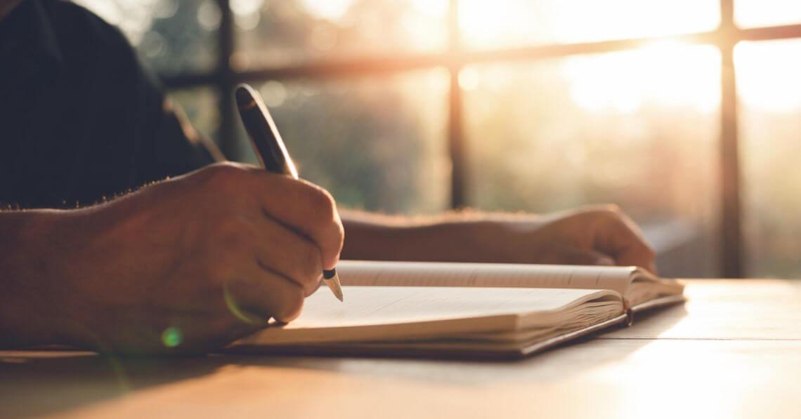 Close up of a man's hand holding a pen over a gratitude journal