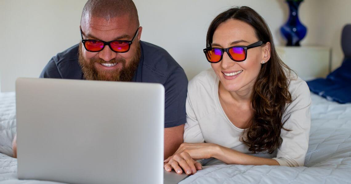 A couple sharing a laptop wearing blue light blocking glasses