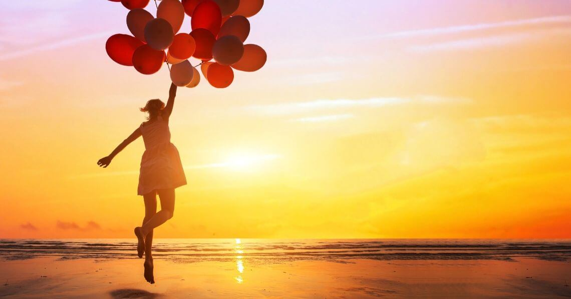 A woman holding onto several red balloons