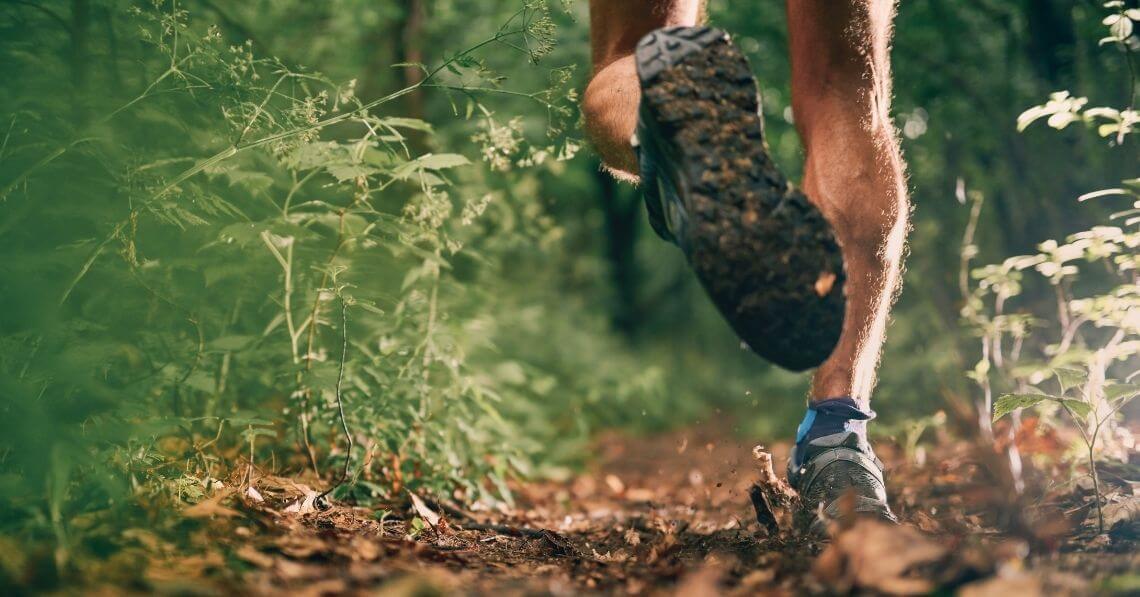 Close up of the shoes of a man running in the forest
