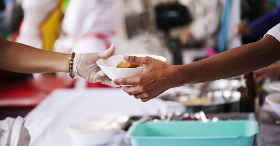 Volunteer serving food to people in need