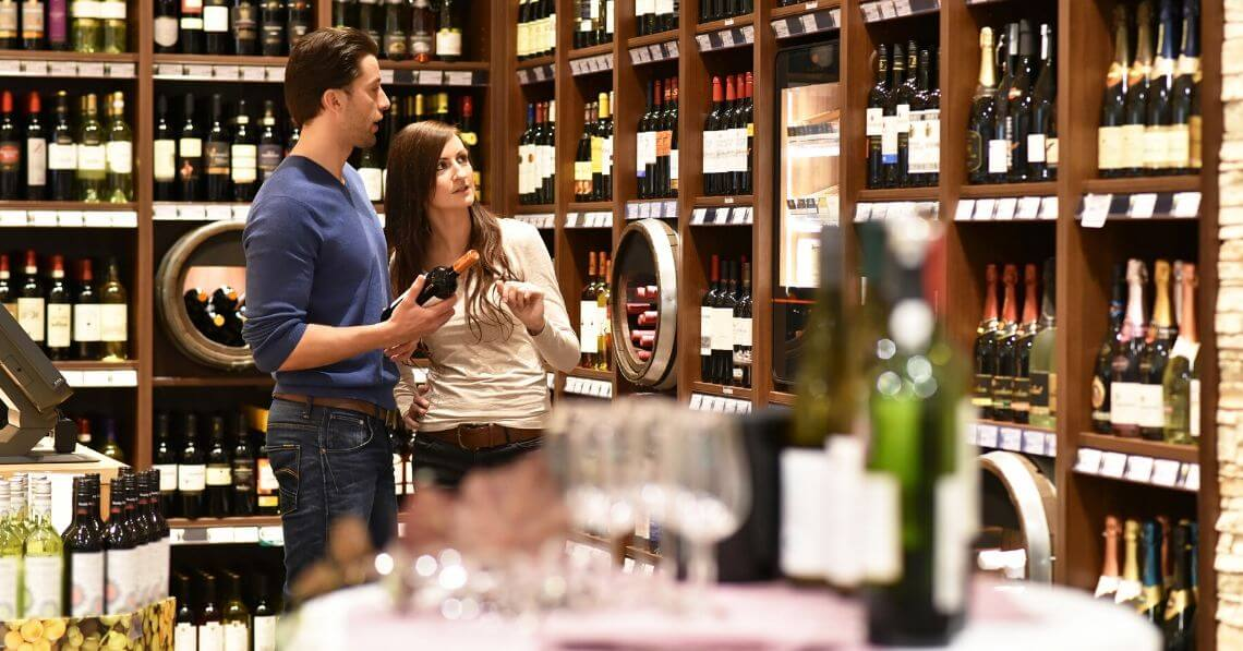 A young couple choosing wine in a store