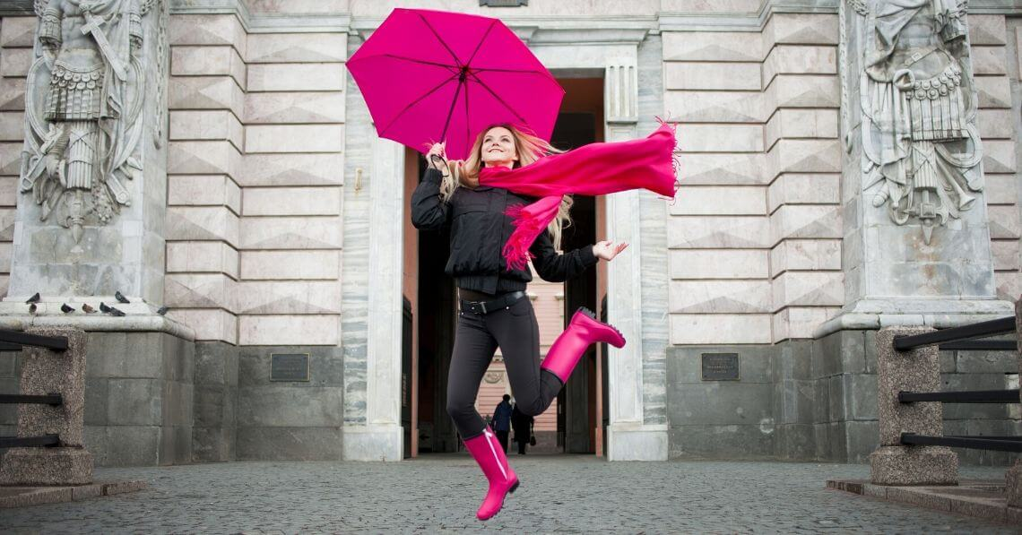 Playful woman jumping in the street with an umbrella