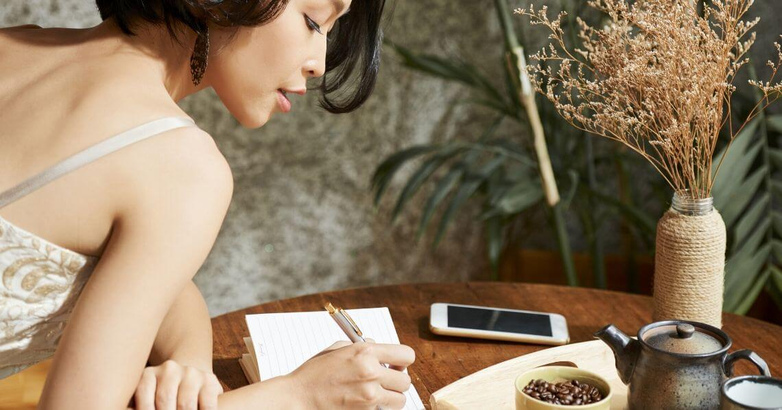 Young woman writing on her gratitude journal