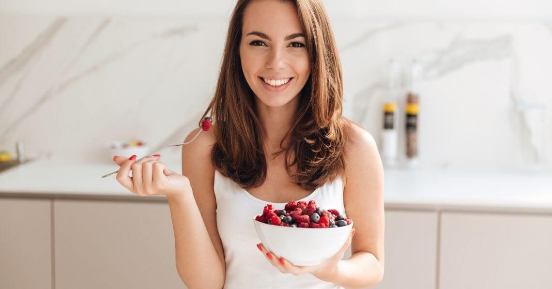 Young woman with a large bowl of berries